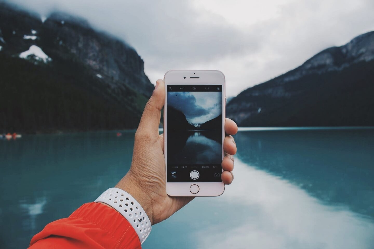 Someone holding an iPhone taking a picture of a lake and mountains