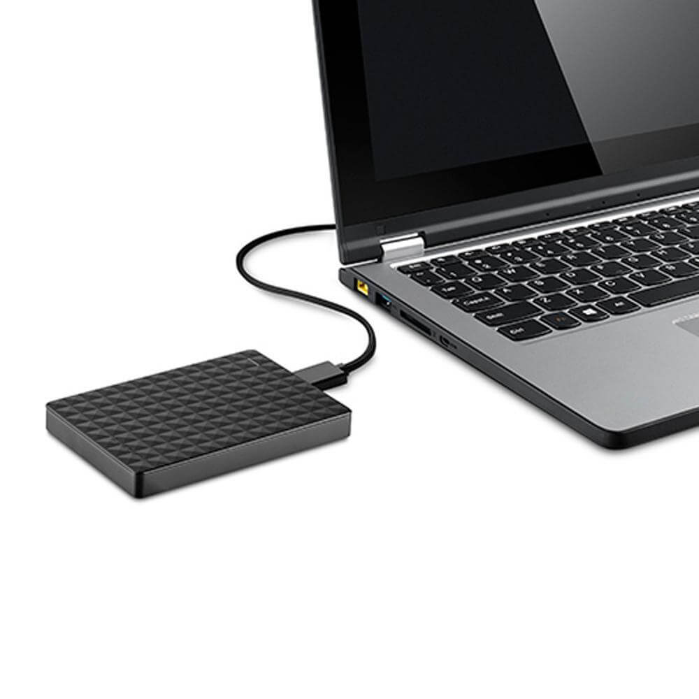 A silver laptop with a black blank screen with an external drive attached to the laptop
