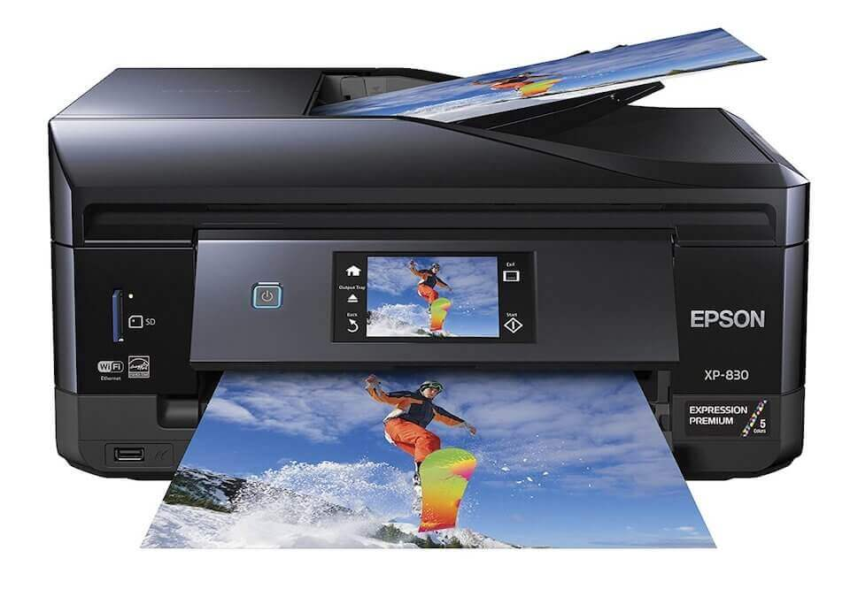 A black printer and scanner that is printing out a colored picture of a snowboarder catching some air
