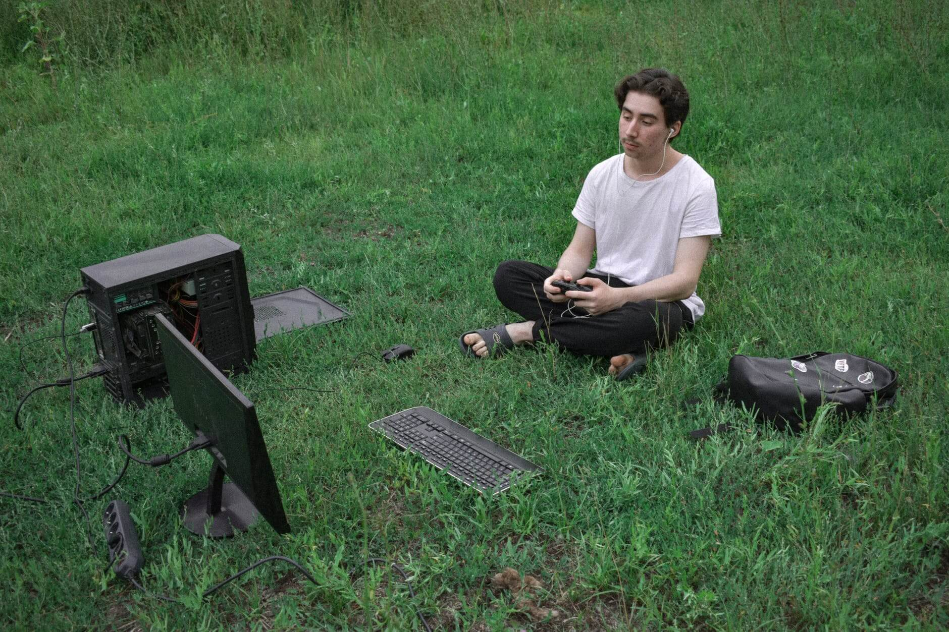 A man sitting on the grass connected to his computer and playing games. Satire.