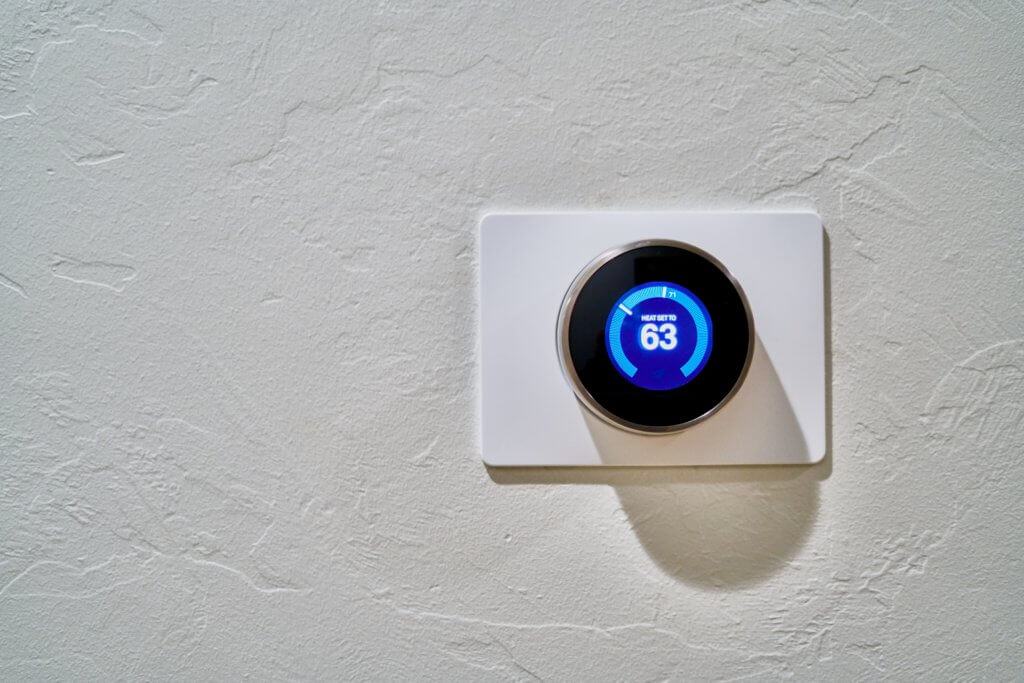 A smart thermostat on a white wall