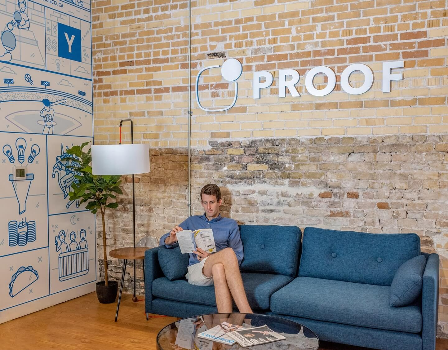 "A man sitting on a blue couch and under a sign that says ""Proof""."