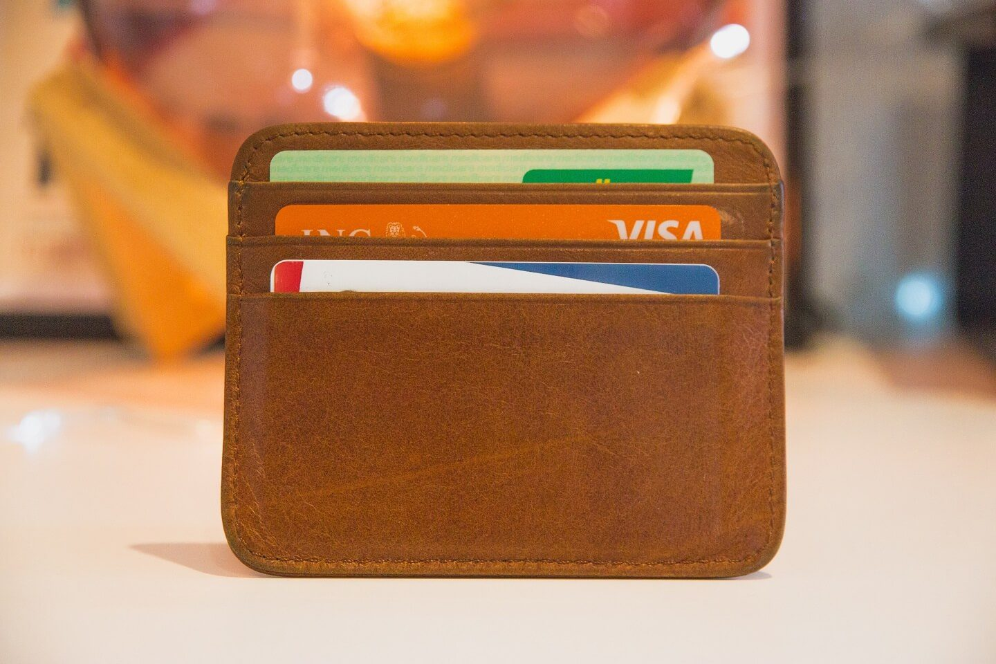 A photo of a brown wallet on a standing up on a desk with 3 credit cards in it.