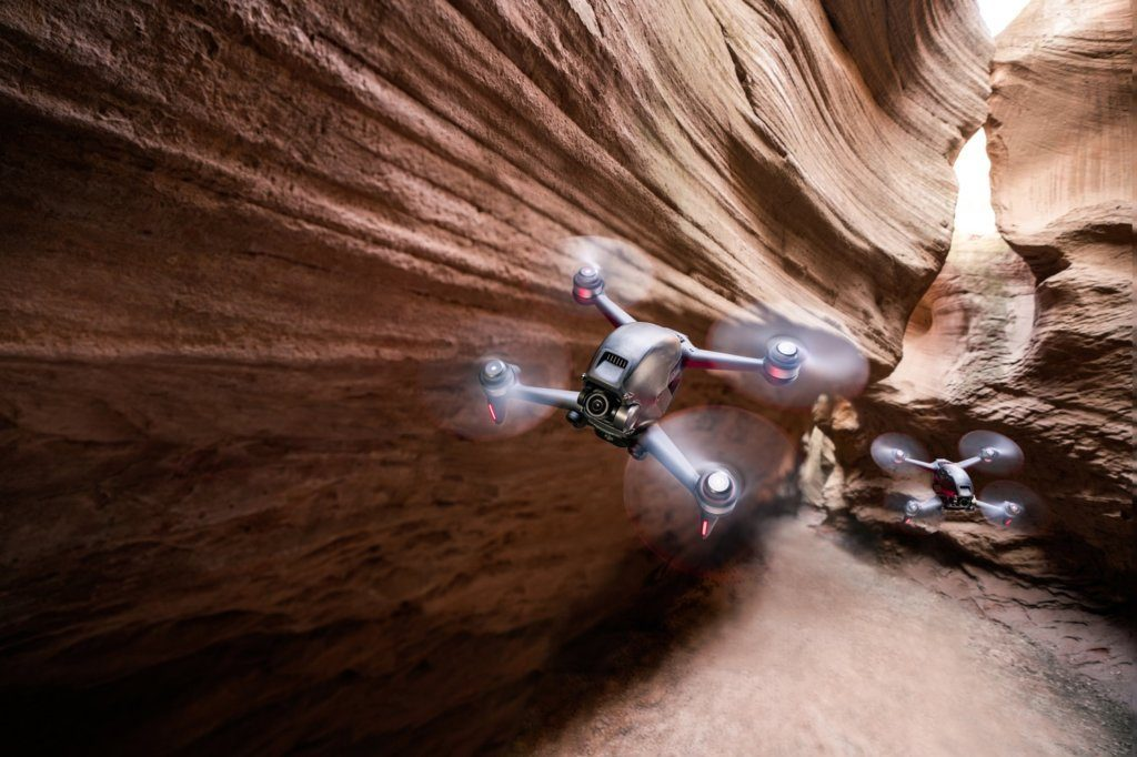 A photo of two drones flying through a sandstone slot canyon.