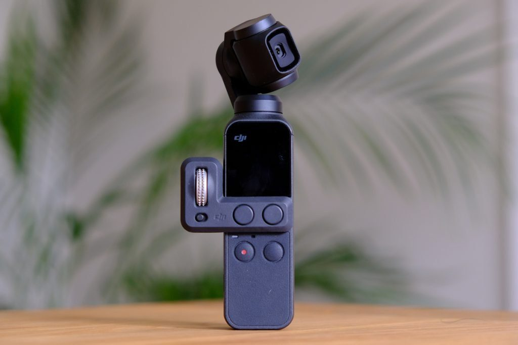 An image of the DJI Osmo Pocket standing on a table with the Controller Wheel accessory.