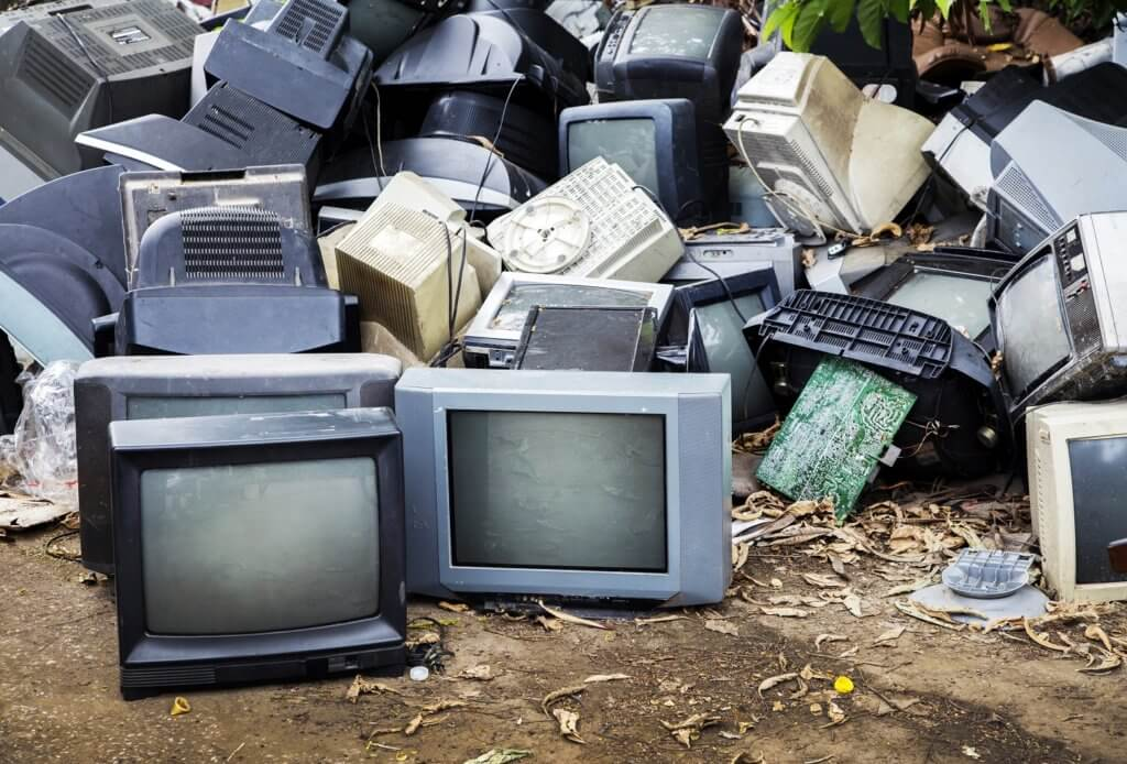 old television electronic waste in garbage on ground