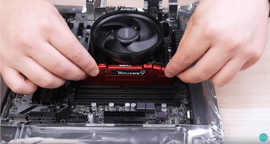 A technician installing RAM into a motherboard