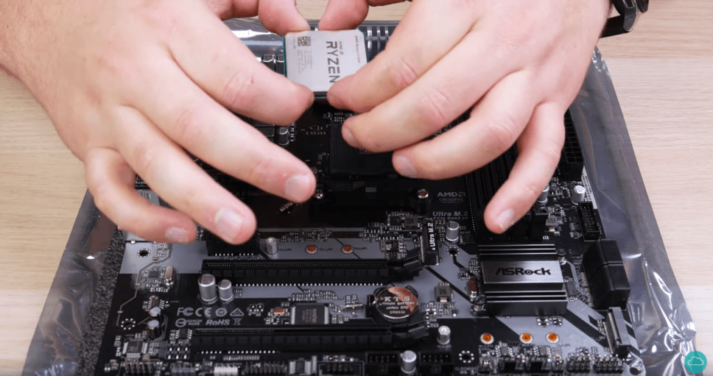 A screenshot of a PC build video with hands holding a CPU before installing into a motherboard