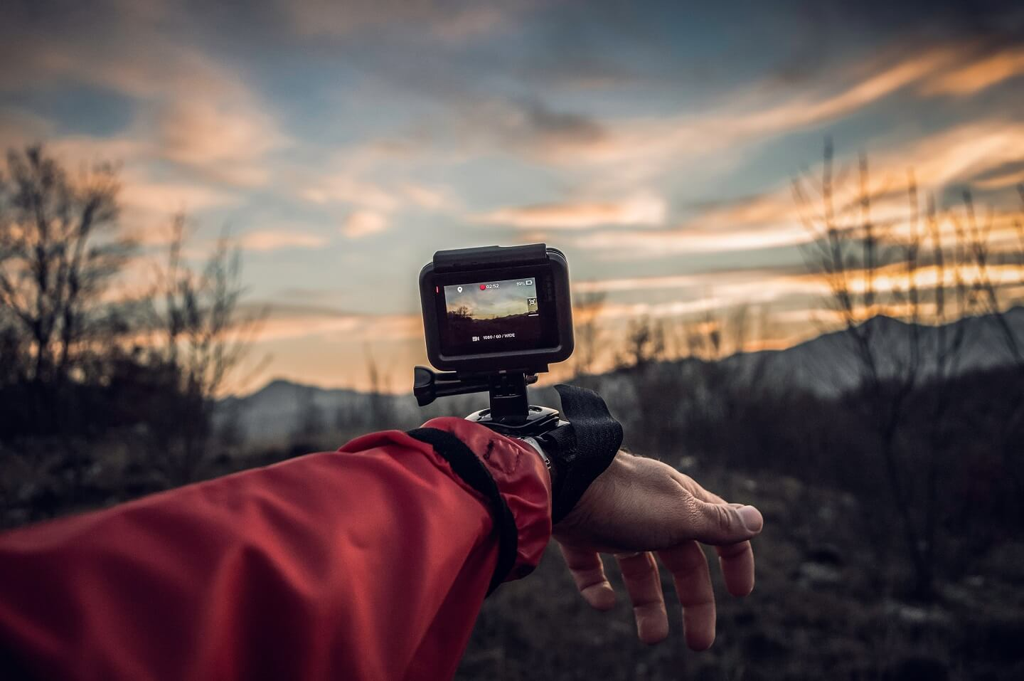 An arm outstretched with a GoPro mounted on the wrist capturing a scenic sunrise in the mountains.