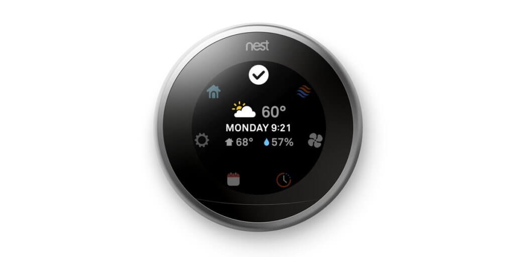 A black Nest Thermostat on a white wall with the temperature, day, time, and weather on the screen