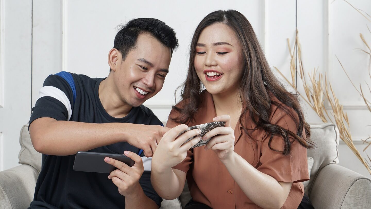A man and woman sitting together smiling and holding their smartphones as the man is pointing to something on the woman's smartphone.