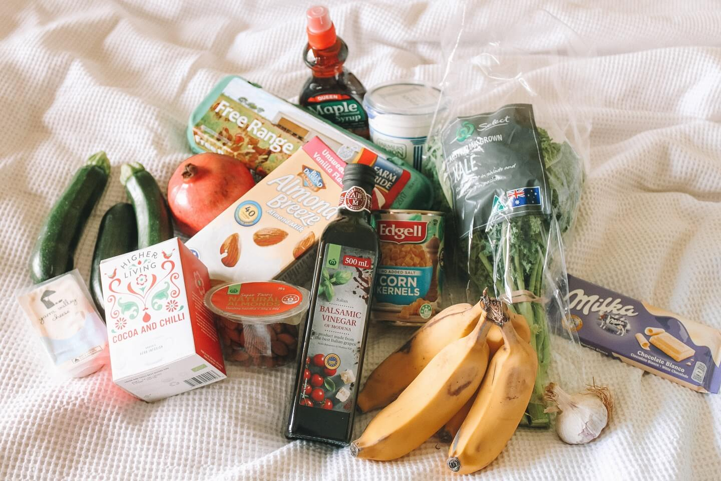 An assortment of fruits, veggies, and food on a display cloth.