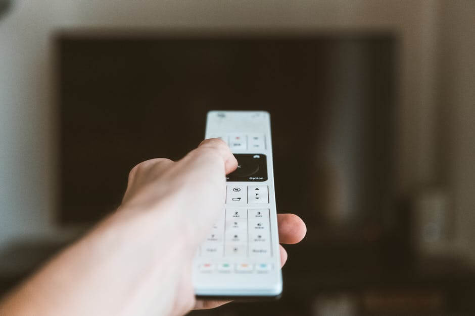 A hand holding a white remote and pointing it at a TV