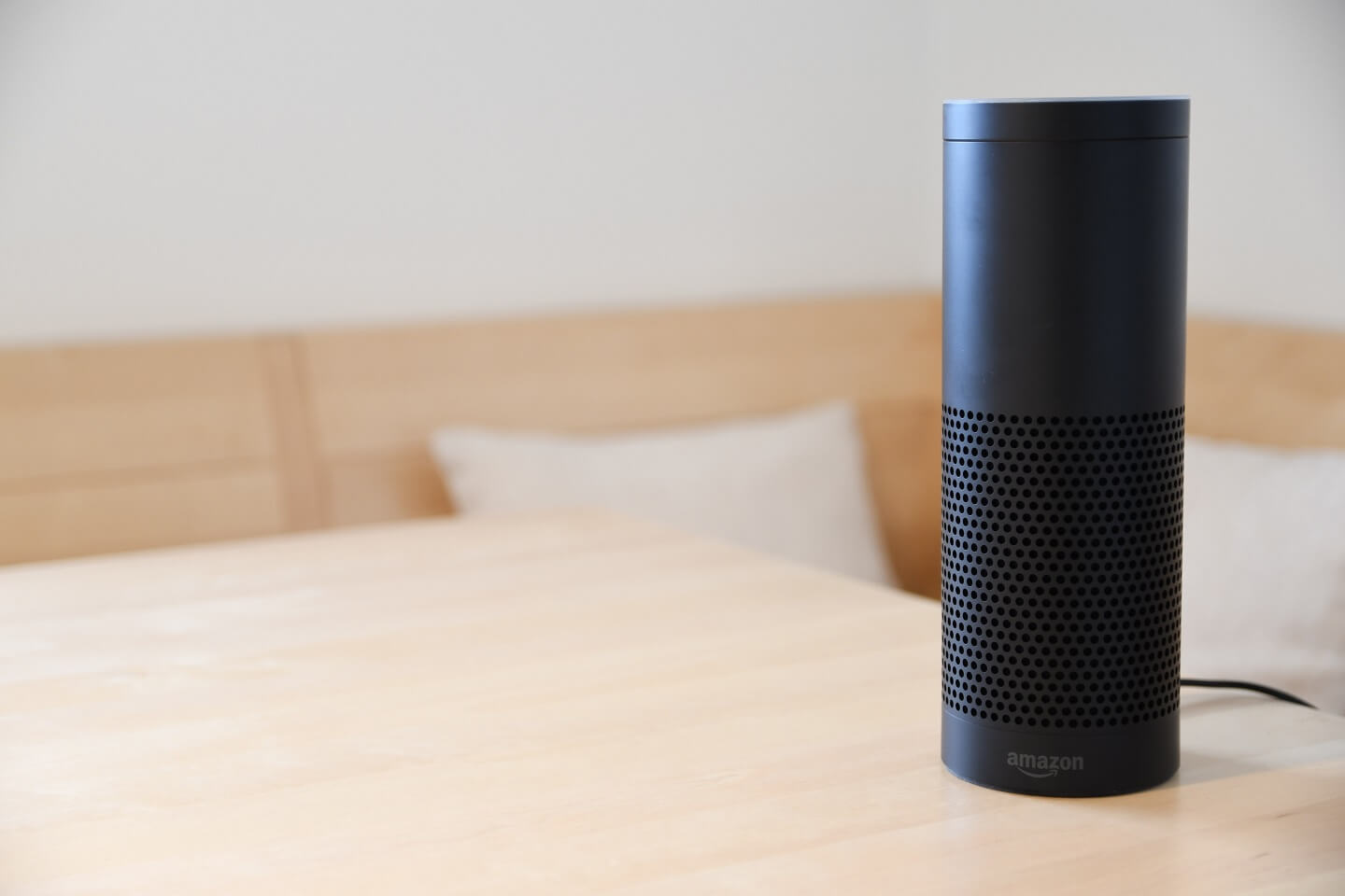 A black Amazon Echo speaker (with Amazon Alexa on it)