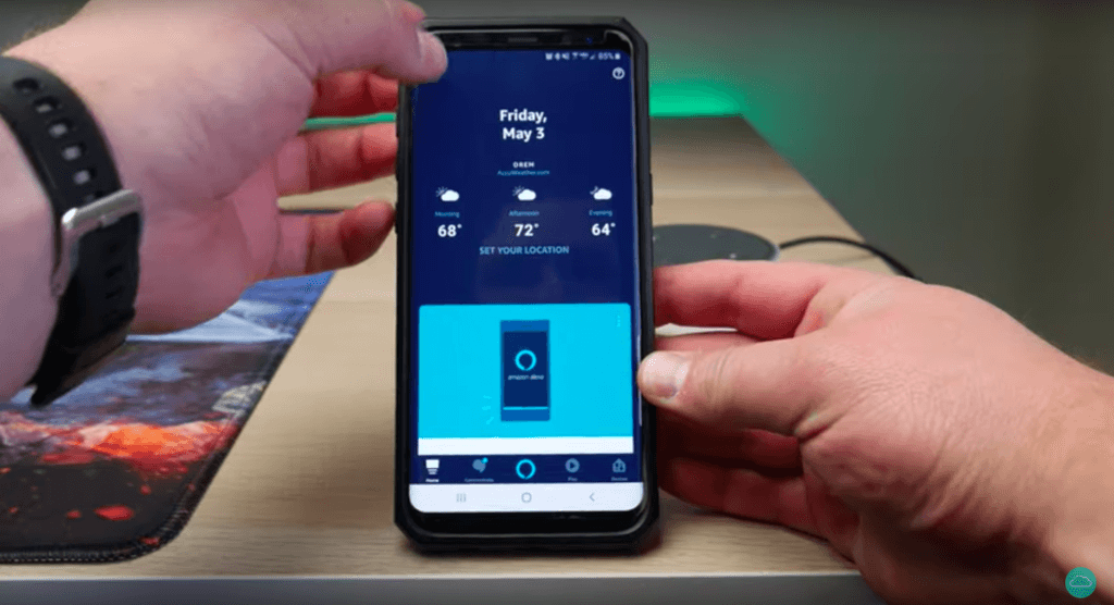Two hands holding a phone with Alexa app open and showing where to locate the menu in top right