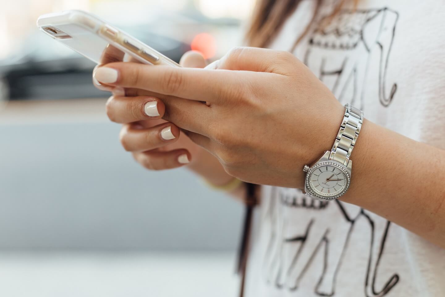 Woman with a silver watch and white tshirt is holding her iPhone in both hands, looking at the screen.