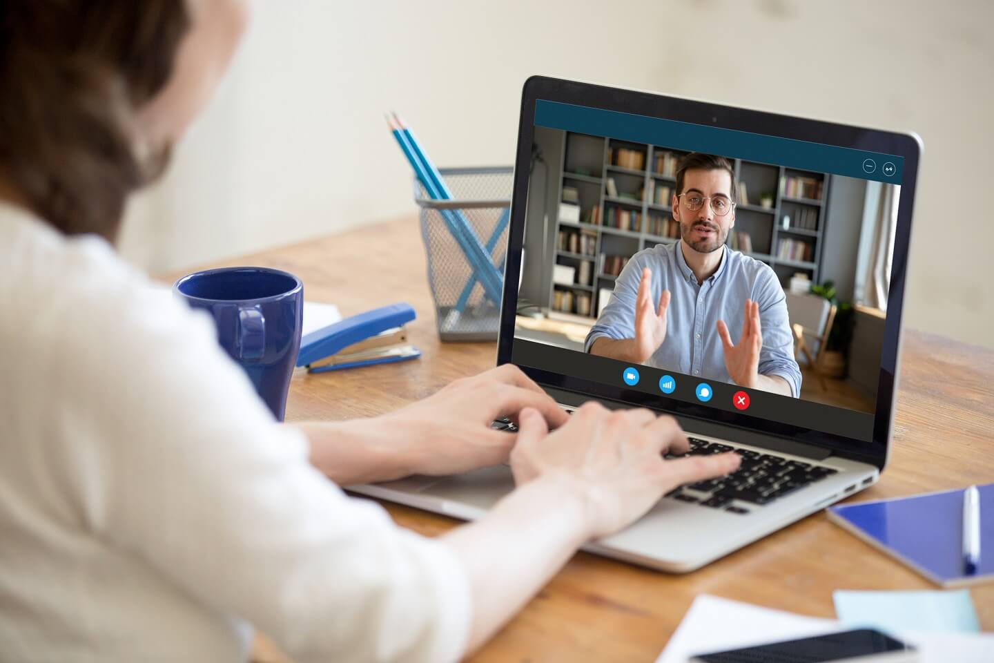 A woman on her laptop video chatting with a man in a blue shirt.