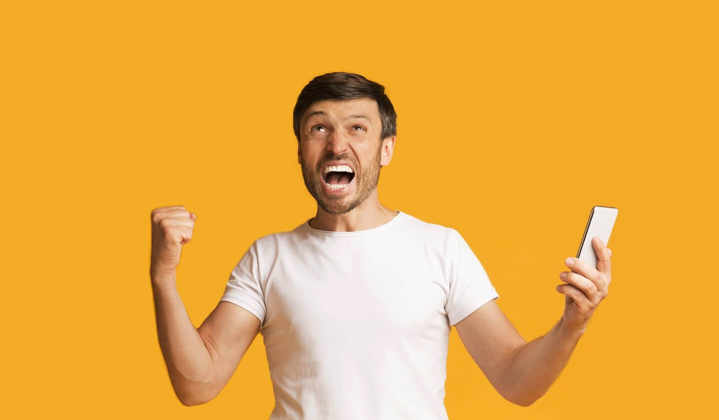 Emotional Man Shouting Holding Smartphone And Shaking Fists Standing On Yellow Studio Background.