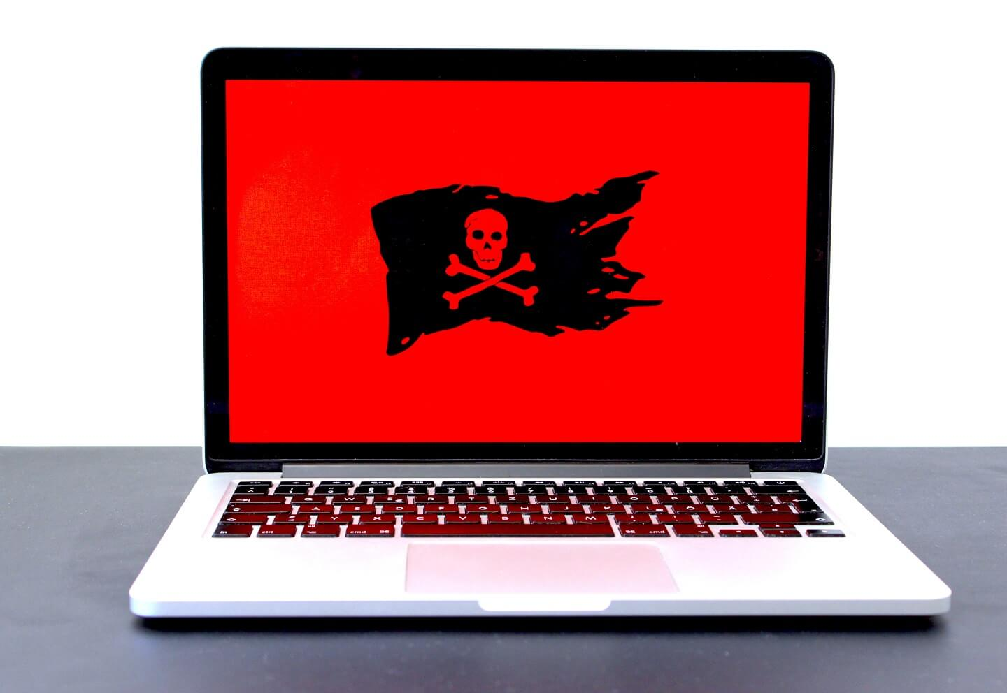 A laptop with a red screen with a pirate flag on it.