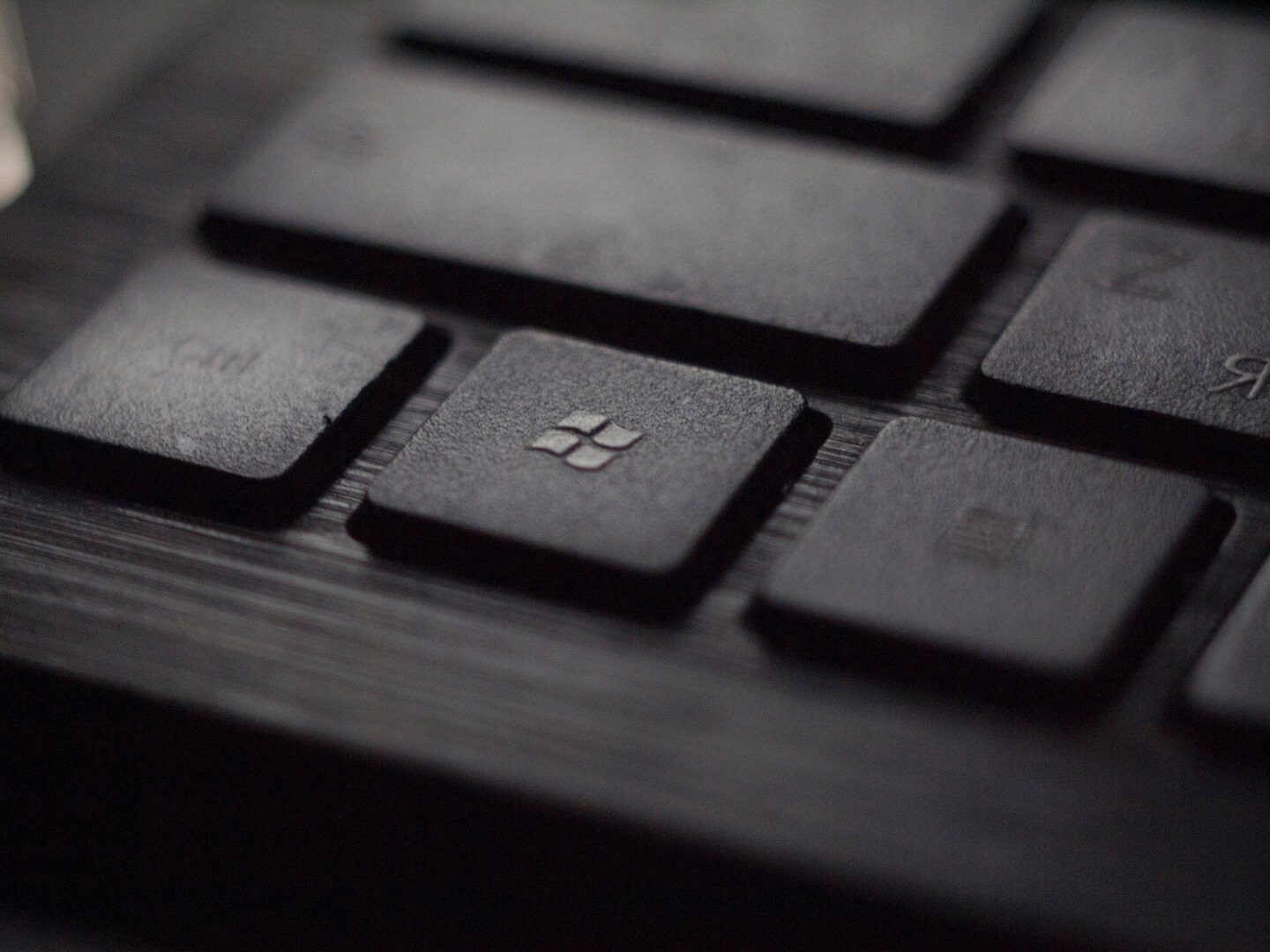 A photo of a black keyboard with the Windows key being the focal point.