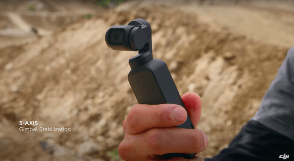"A hand holding the DJI Osmo Pocket with the label ""3-axis Gimbal Stabilization""."