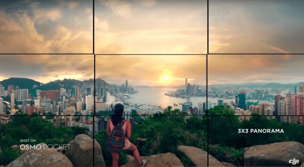 An Osmo Pocket panorama shot with a lady standing on top of a hill looking out over a city.