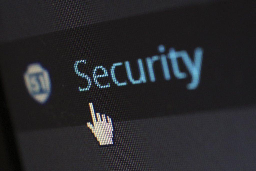 "A photo of a computer screen with the word ""security"" and a mouse hand hovering over the word."