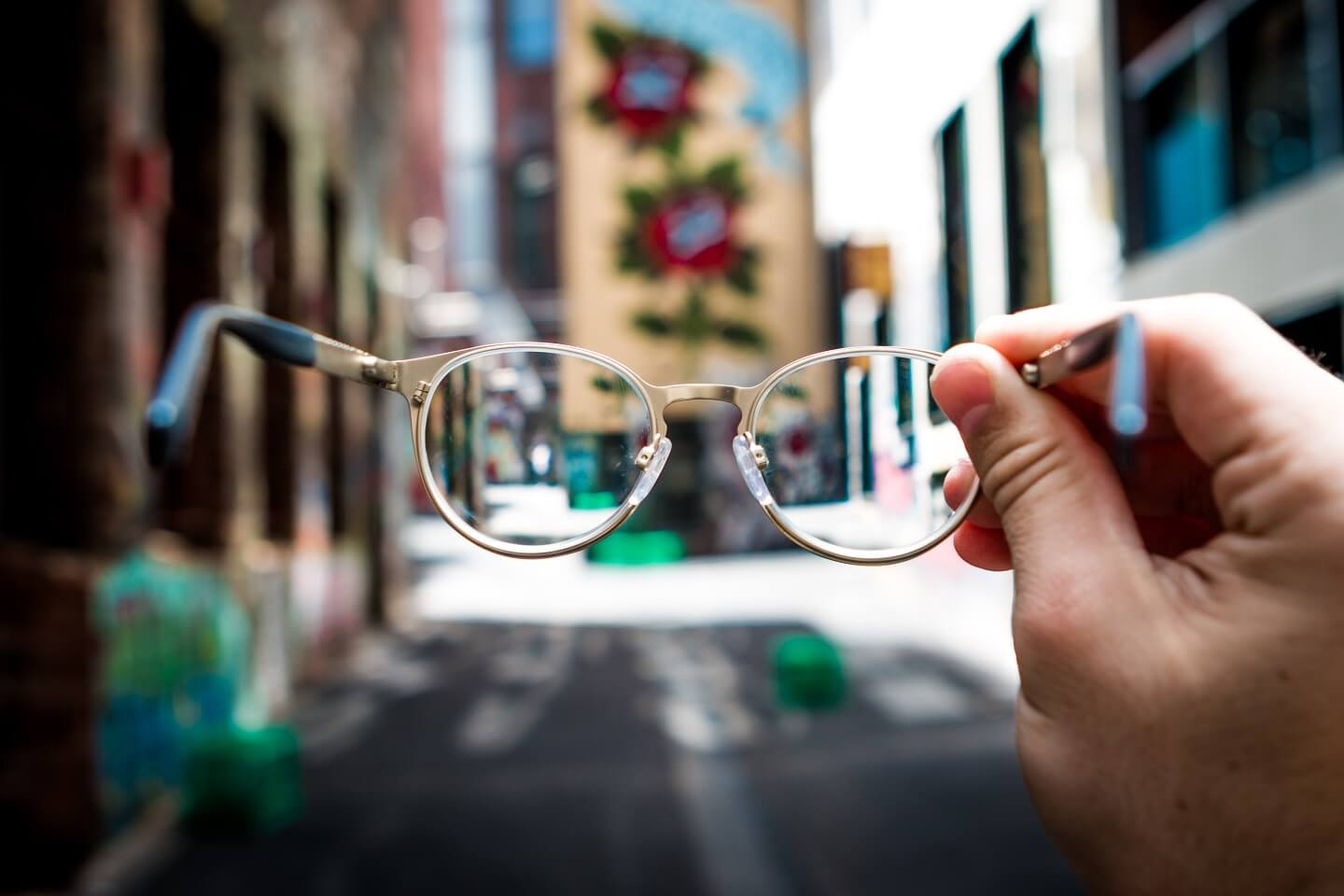 A hand holding up a pair of glasses standing on a empty road in the city