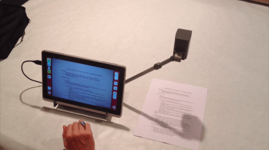 A sight enhancement tool that is on a table magnifying a paper on the desk and displaying it on the screen.
