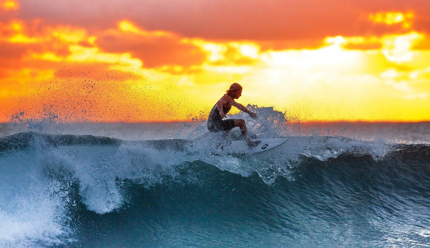 A surfer on top of a wave with a golden sunset in the background