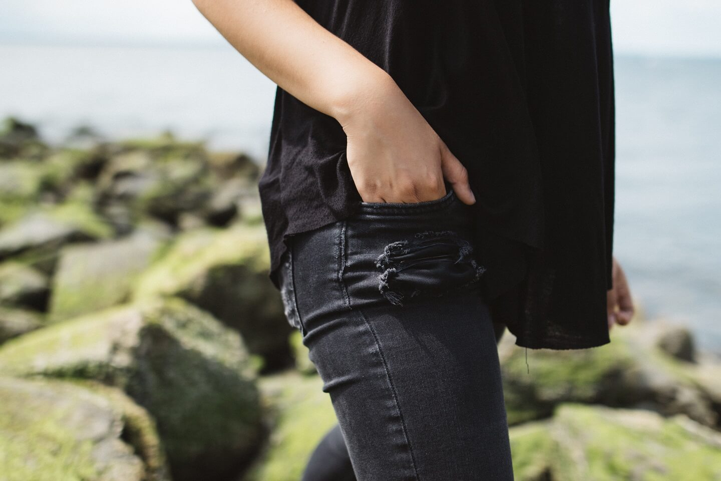 A person walking in black jeans and shirt with a hand in their pocket.