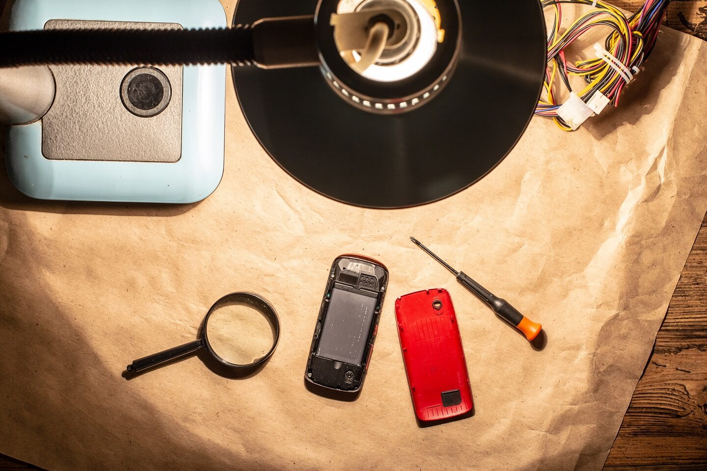 A birds-eye view photo with a lamp lighting a desk with a phone and tools