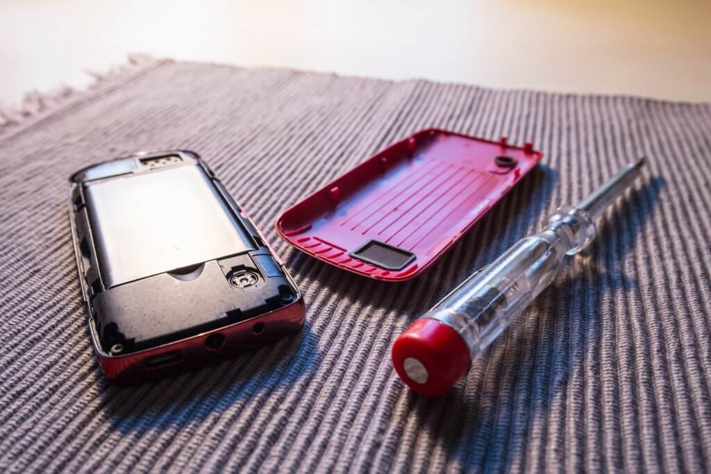 Concept - the right to repair. Mobile phone with an open case and a screwdriver as a symbol of fixing of consumer electronics and appliances.