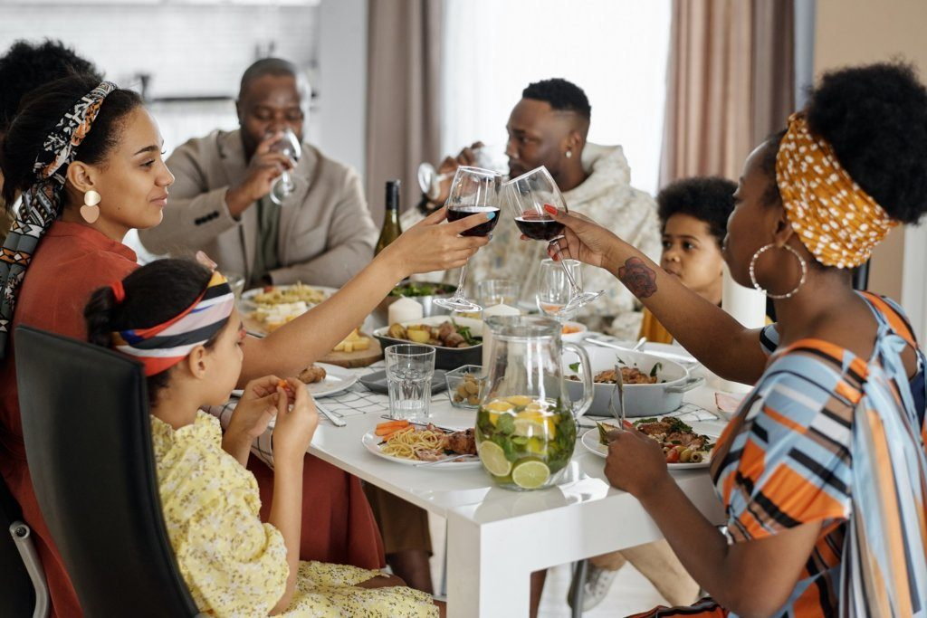 A family having a toast while around the dinner table.