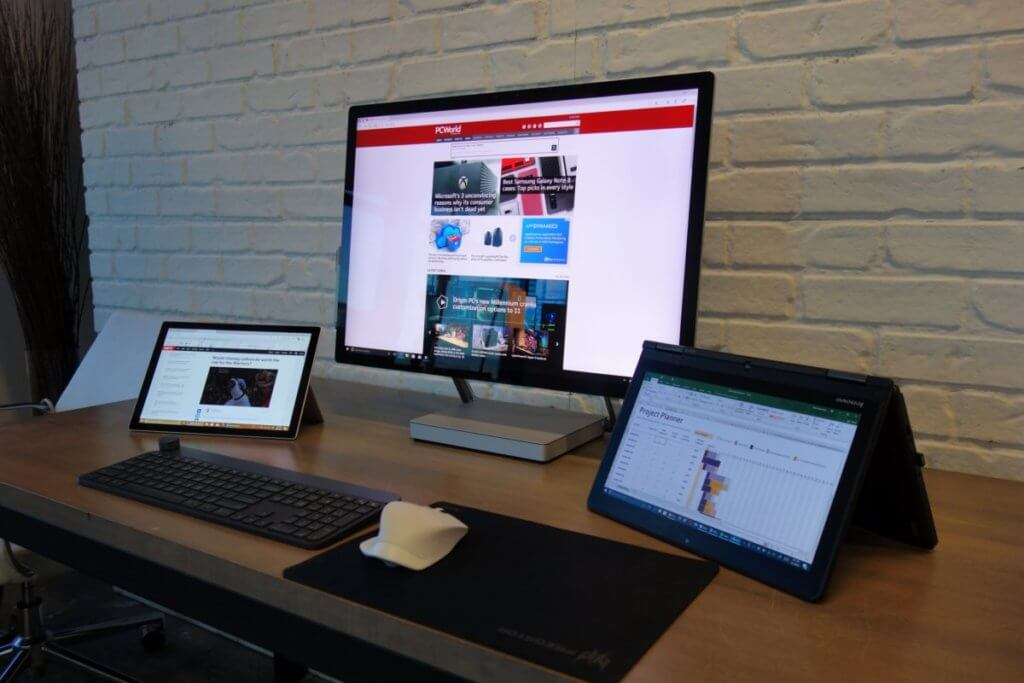 A desk with two tablets and a large screen monitor on it.