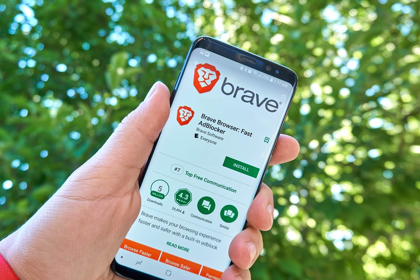 A hand holding a mobile device with the Brave browser app open and on the screen.