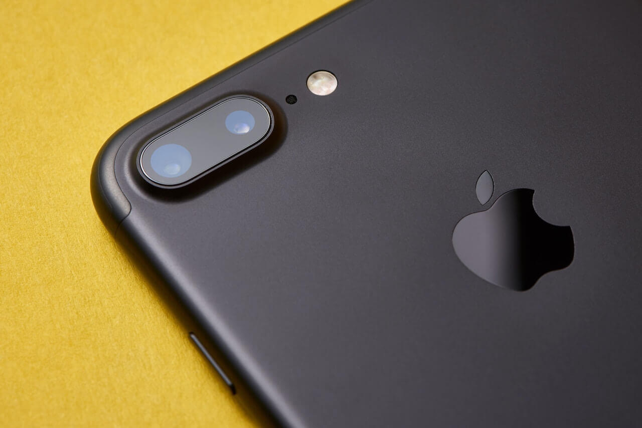 An black iphone7 on it's face showing the camera and apple logo on the back on the phone
