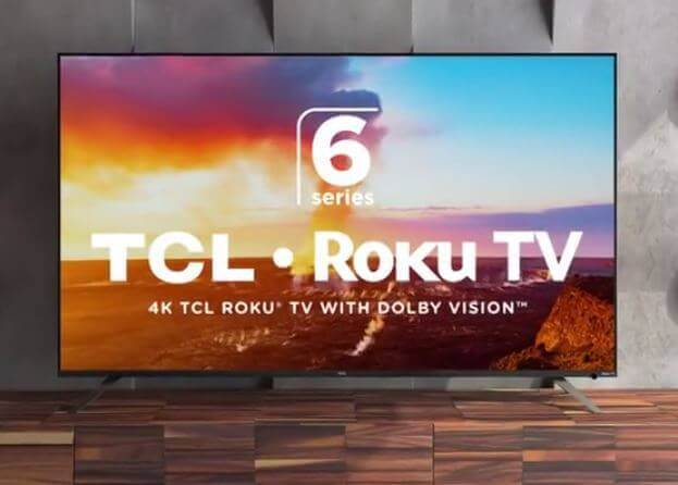 "A flatscreen smart Roku TV sitting on a brown tiled floor and the screen shows ""6 Series, TCL, Roku TV, 4K TCL Roku, TV With Dolby Vision"""