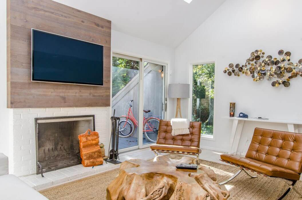 A nice living room with brown lounging chairs and a flatscreen smart TV above a fireplace