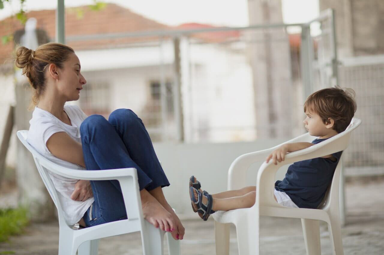 A grown woman and a small boy sitting in white lawn chairs, facing each other and the lady is speaking to the boy about something serious.