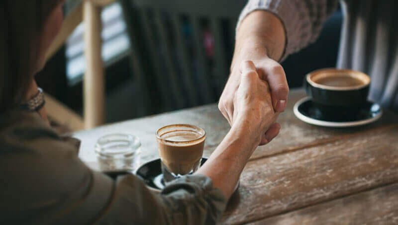 A man and a woman sitting at a table with coffee and reaching across the table and shaking hands