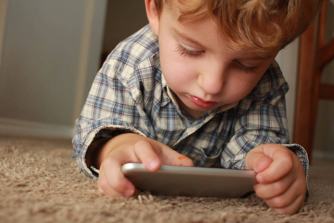 A toddler on the carpet looking at and holding a silver mobile device