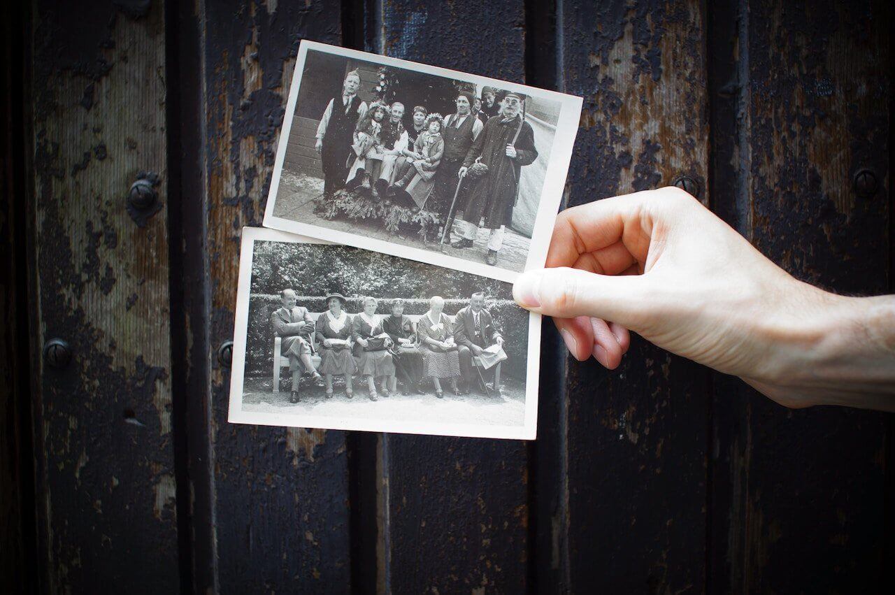 A hand holding two antique family photos with a wood paneled background