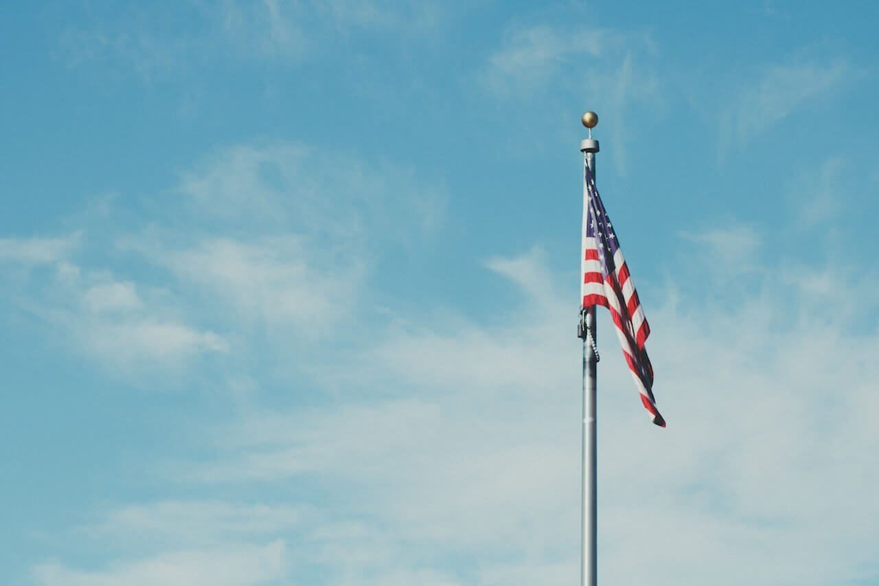 An American flag on a pole with a blue sky background