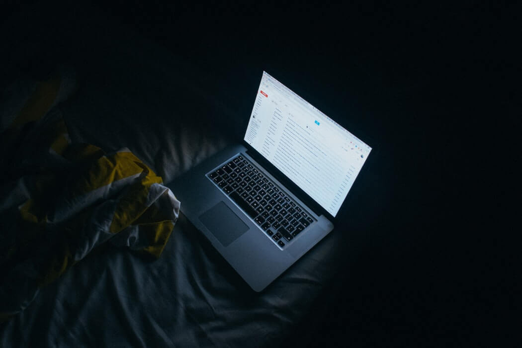 An open and turned on laptop sitting in the dark on a bed
