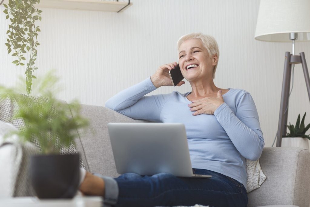 Woman on phone using laptop and laughing