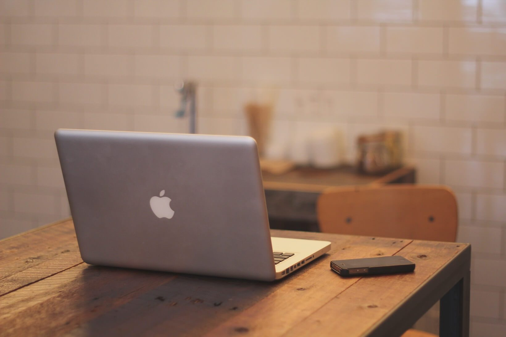 a macbook sitting on a brown table in a kitchen with a phone next to it