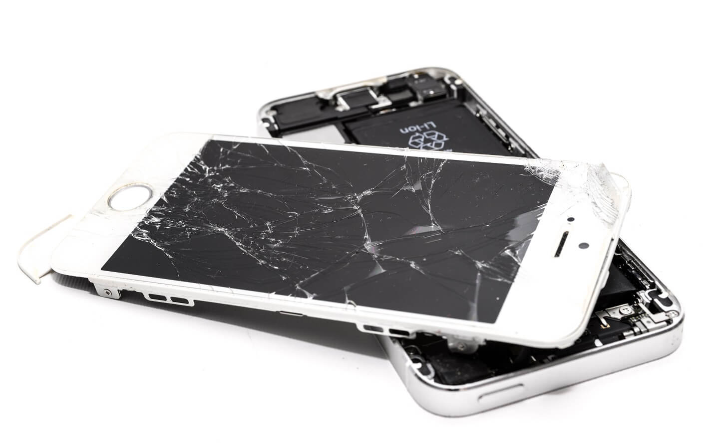 A white iphone taken apart and with a cracked screen.