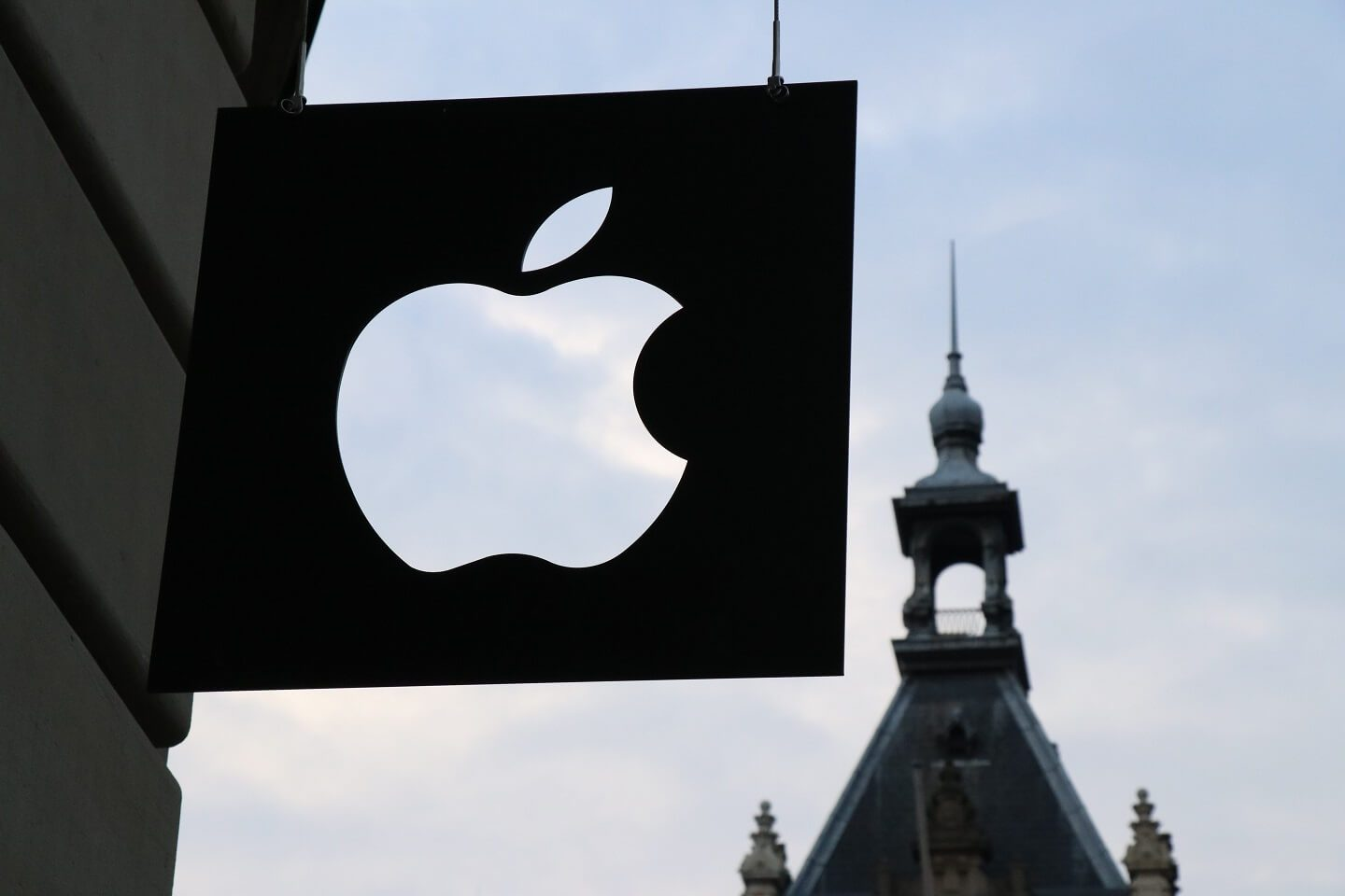 An apple storefront black sign with the apple logo cut out of it.