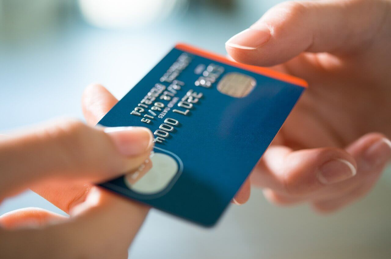 A person handing a blue credit card to another person (the image only shows their hands).